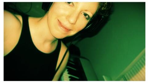 Elizabeth Joan Kelly, candid head shot with keyboard, color